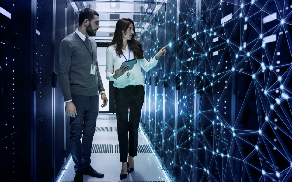 Two people walking through server room | internet services orlando